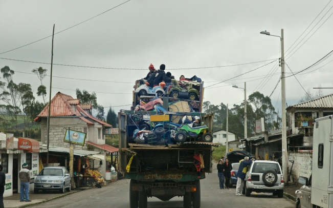 children in toy trucks on top of a moving truck!- the road to Chimbo