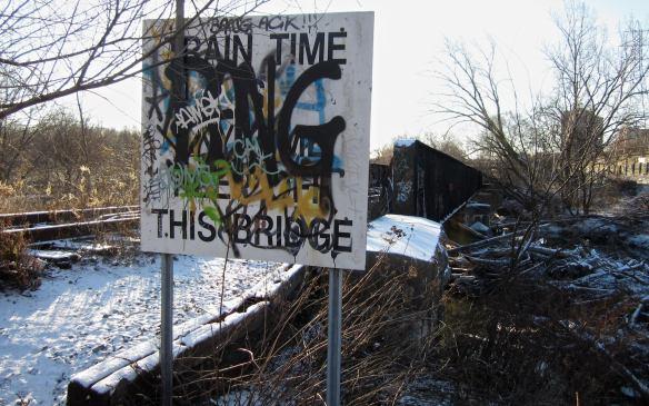 warning sign on east side of Metrolinx rail bridge