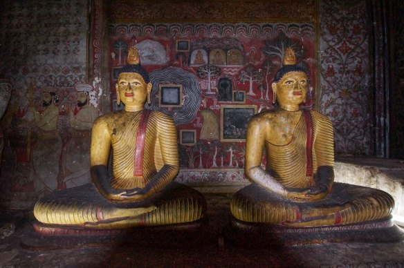 two seated Buddhas in front of garden mural