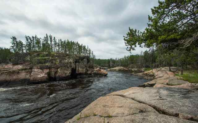 looking down  to the canoe and Max at Island Chutes Rapids on the Bloodvein