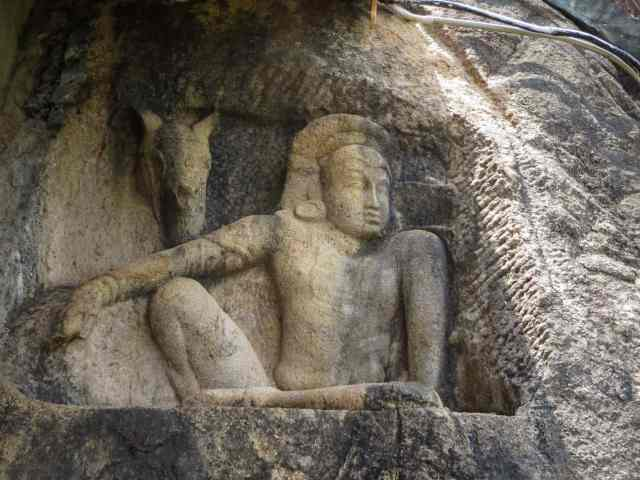 carving of seated man with horse at Isuruminiya Vihara