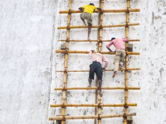 close up of workers on bamboo ladder