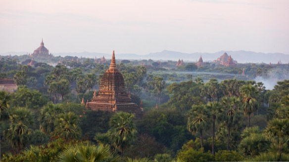 early morning mist and smoke rise over Bagan fields
