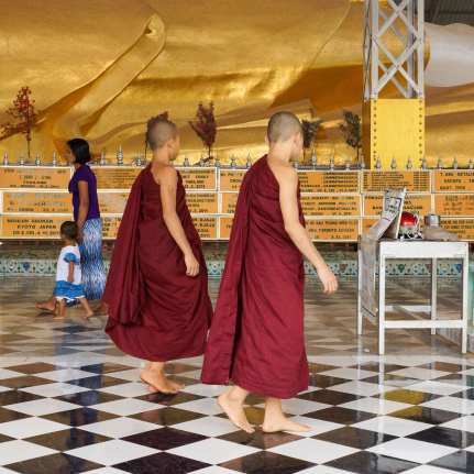 a couple of novice monks walk by the Shwethalyaung Buddha