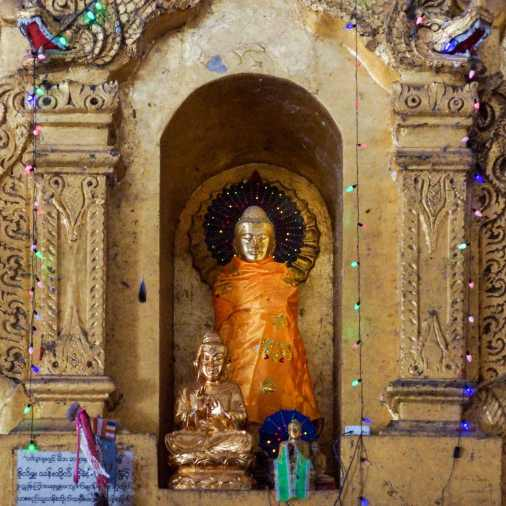 Buddha figures in a niche of the Hintha Gon shrine surrounded by colourful lights