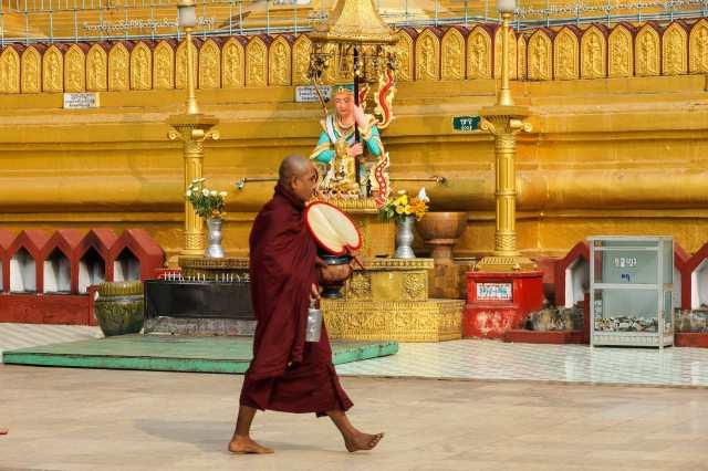 monk walks past a planetary post shrine