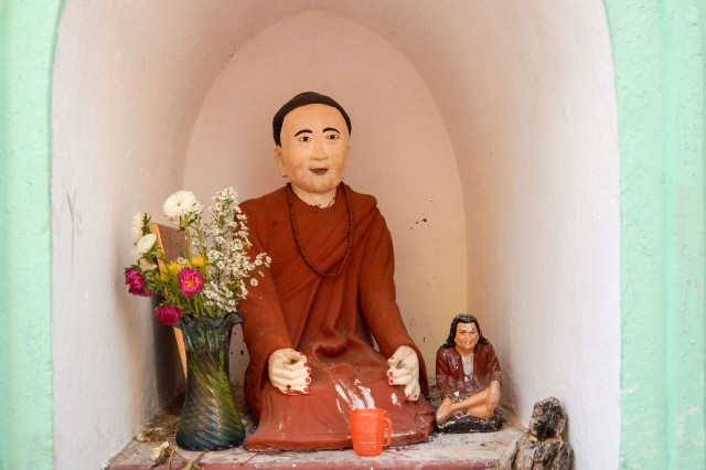two nat figures and a wooden Buddha statue