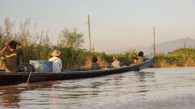Intha family on Inle Lake in long boat
