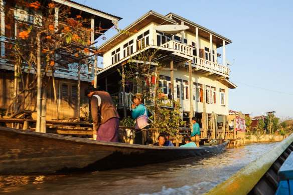 local boat passes us by in narrow Inle Lake channel