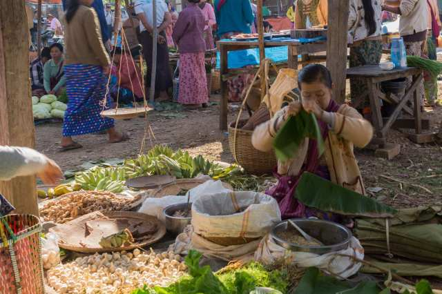 Inle market woman preparing bamboo leaf wrappings