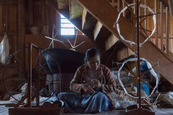 weaver preparing thread at weavers' cttage - In Phaw Khone