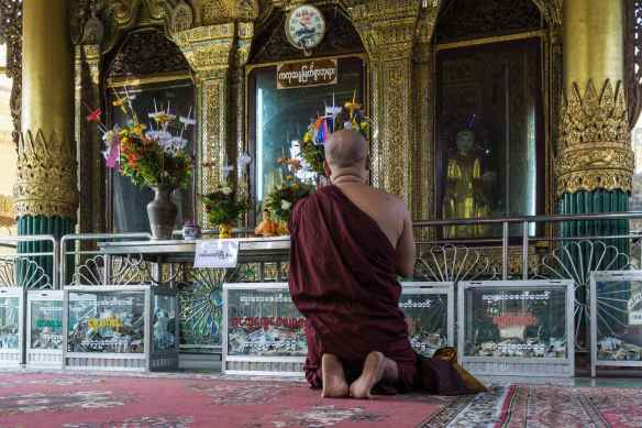 monk prays at one of Sule Paya's shrine rooms