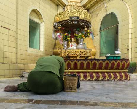 prayer at one of the Sule Paya's eight planetary posts