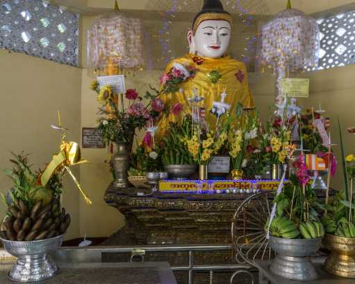 Sule Paya shrine room with seated Buddha figure and offerings