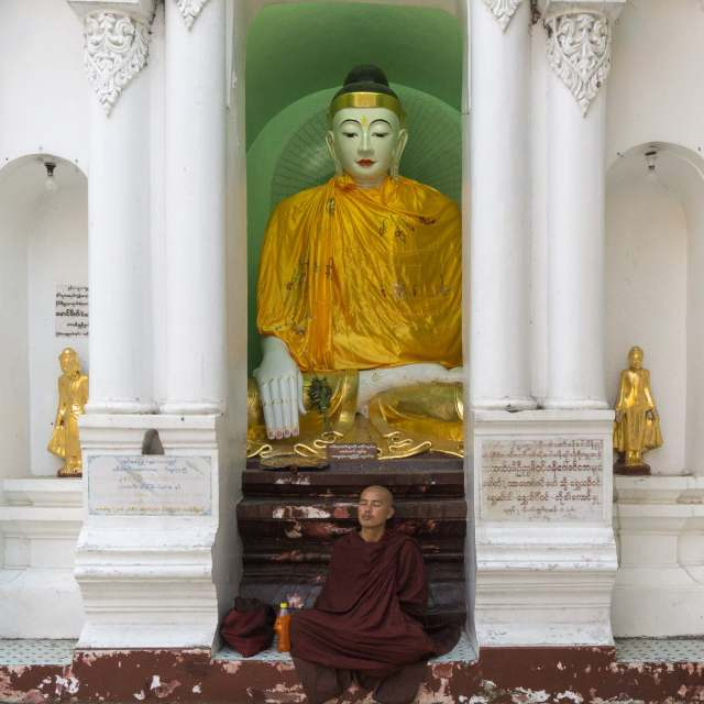 monk at Shwedagon under a Buddha statue